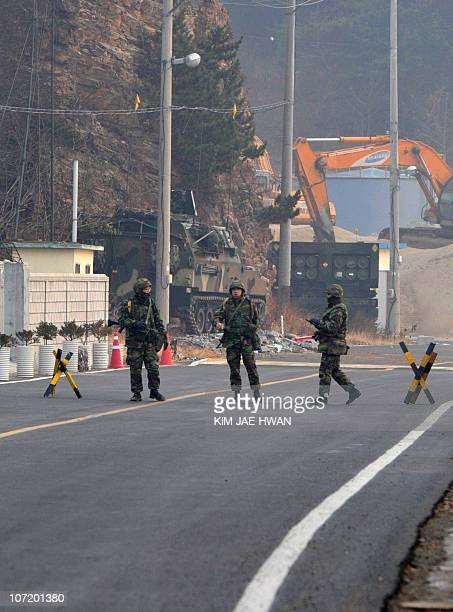 South Korean Marines stand guard at a check point along a road on Yeonpyeong island on November 30 2010 South Korea deployed rocket launchers and...