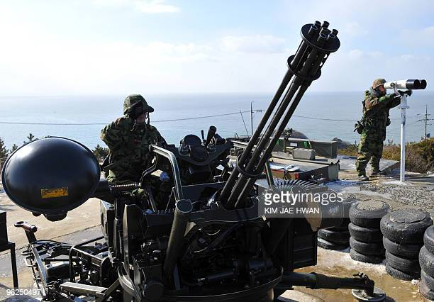 South Korean marines stand guard at an antiaircraft gun position on Yeonpyeong Island in the disputed waters of the Yellow Sea on January 29 2010...