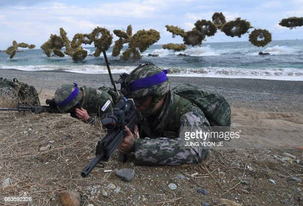 TOPSHOT South Korean Marines take position on a beach as amphibious assault vehicles fire smoke shells during a joint landing operation by US and...