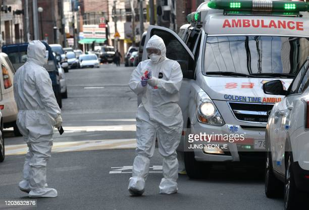 South Korean medical workers wearing protective gear carry samples as they visit a residence of people with suspected symptoms of the COVID-19...