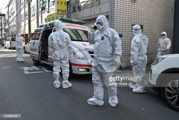 South Korean medical workers wearing protective gear visit a residence of people with suspected symptoms of the COVID-19 coronavirus to take samples,...