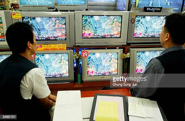 South Korean men watch a satellite photo of the train explosion in North Korea on televisions at an electronic department store on April 23 2004 in...