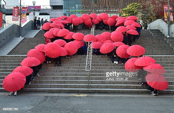 South Korean middle school students hold umbrellas as they form a giant red ribbon during a ceremony to mark World AIDS Day in Seoul on December 1...