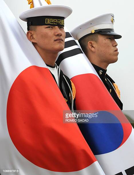 South Korean military honour guards carry Japanese flags as they await the arrival of Japan's Prime Minister Naoto Kan at Seoul air base for the G20...