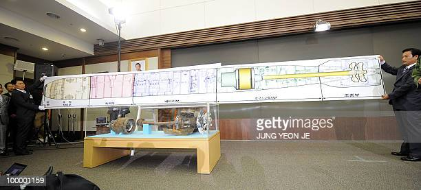 South Korean military officers shows a realsize blueprint of a torpedo above torpedo parts salvaged from the Yellow Sea during a press conference at...