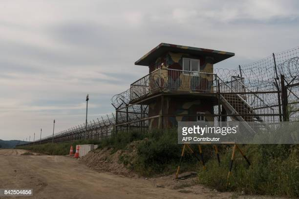 A South Korean military post stands before the barbedwire fence of the Demilitarized zone separating North and South Korea on Ganghwa island on...