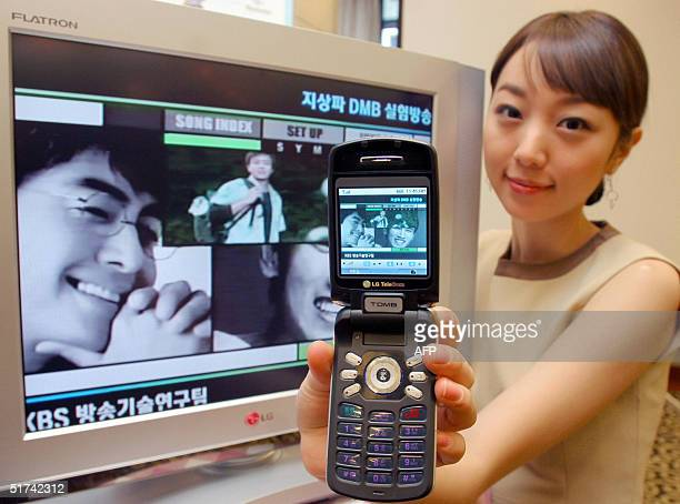 South Korean model displays a LG Electronic new DMB mobile phone handsets which can show television broadcasts real time during an exhibition in...
