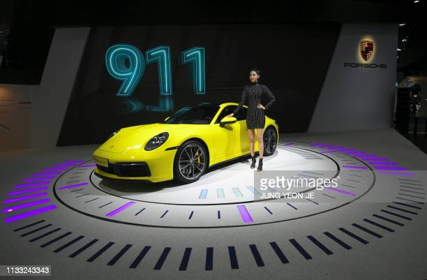 A South Korean model poses with a Porsche 911 Carrera S during a press preview of the Seoul Motor Show in Goyang northwest of Seoul on March 28 2019...