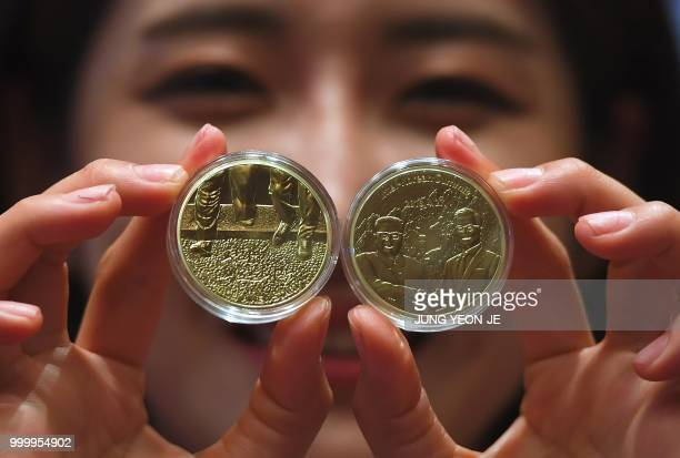A South Korean model shows medallions commemorating the historic interKorean summit between Moon Jaein and Kim Jong Un during an unveiling ceremony...