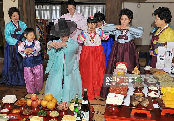South Korean models demonstrate 'charye' a traditional ritual service of food and offerings to thank their ancestors ahead of the Lunar New Year's...