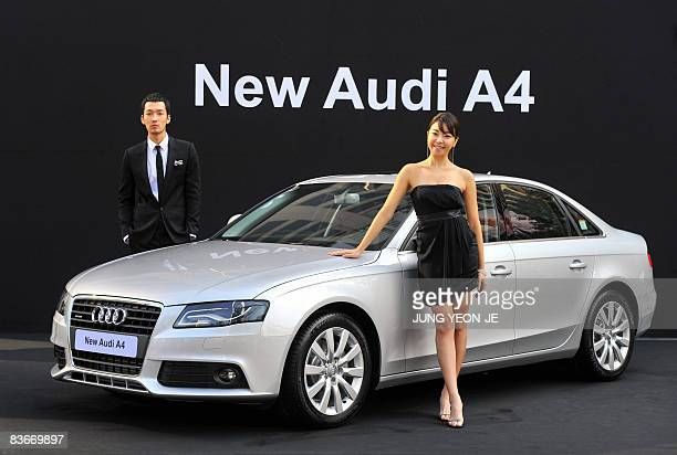 South Korean models pose with German Audi Motorsnew A4 sedan during an unveiling show in Seoul on November 13 2008 The new A4 car is equipped with a...
