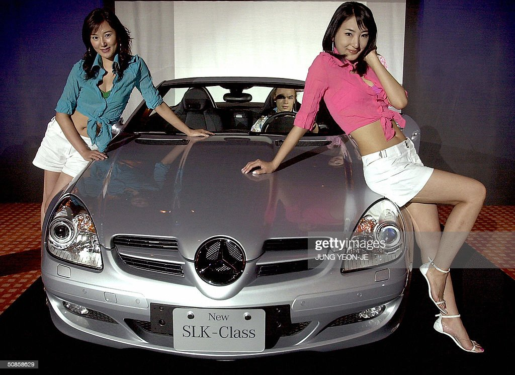South Korean models pose with Germany's Mercedes-Benz new model the SLK 200 during a press unveiling show at a hotel in Seoul, 20 May 2004. The price of the new SLK 200 car, equipped with 1,800 CC engine, is 66,9 million won (56,762 USD) import dealer say.
