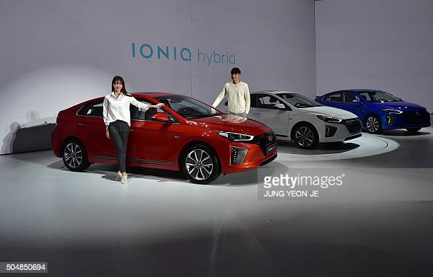 South Korean models pose with Hyundai Motor's new green car model 'Ioniq hybrid' during the unveiling in Seoul on January 14 2016 The Ioniq equipped...