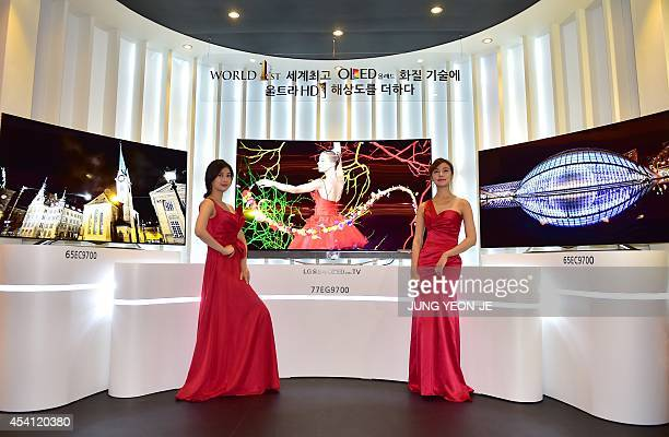 South Korean models pose with LG's 77inch and 65inch Ultra OLED TVs during their unveiling ceremony in Seoul on August 25 2014 LG Electronics...