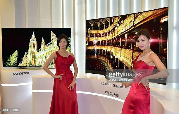 South Korean models pose with LG's 77inch and 65inch Ultra OLED TVs during its unveiling ceremony in Seoul on August 25 2014 LG Electronics announced...