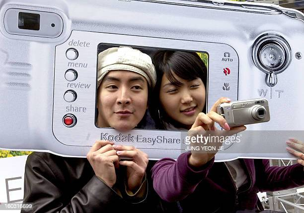 South Korean models show a new 4megapixel Kodak digital camera during a street promotion in downtown Seoul 24 March 2004 The new product LS743 hit...