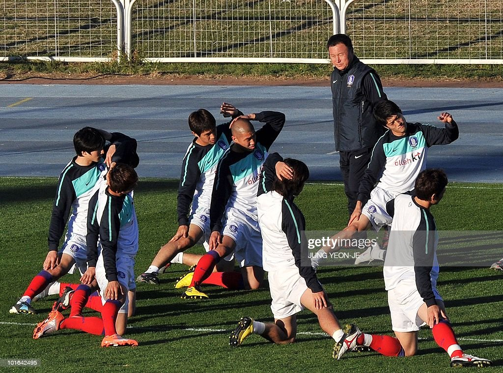 South Korean national football team players stretch as head coach Huh Jung-Moo (top) looks on during a training session at the Olympia Park Stadium in Rustenburg on June 5, 2010. The team arrived in South Africa for the 2010 World Cup.