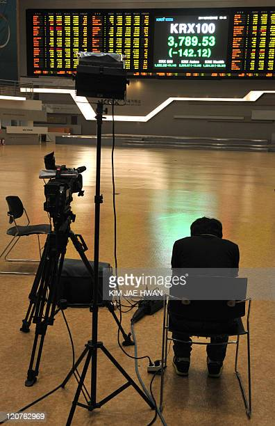 A South Korean news cameraman looks at a stock market board at the Korea Exchange on August 9 2011 The KOSPI index ended down 6810 points at 180135...