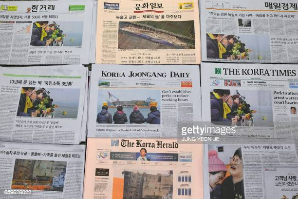 South Korean newspapers carry frontpage stories about bone fragments found from the sunken Sewol ferry and pictures of relatives of the missing...