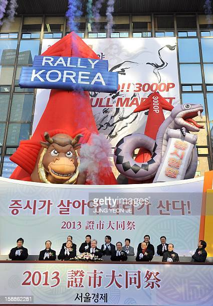 South Korean officers celebrate under balloons of a large bull and a snake to illustrate their desire for a bullish market in the Chinese lunar year...