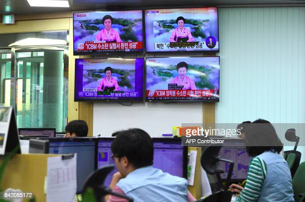 South Korean officials work in front of television news channels showing North Korea's broadcast claiming their successful nuclear test, at the Korea...