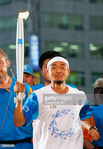 South Korean Olympic torch bearer and 2001 Boston Marathon winner Lee BongJu carries the torch during day five of the Athens 2004 Olympic Torch Relay...