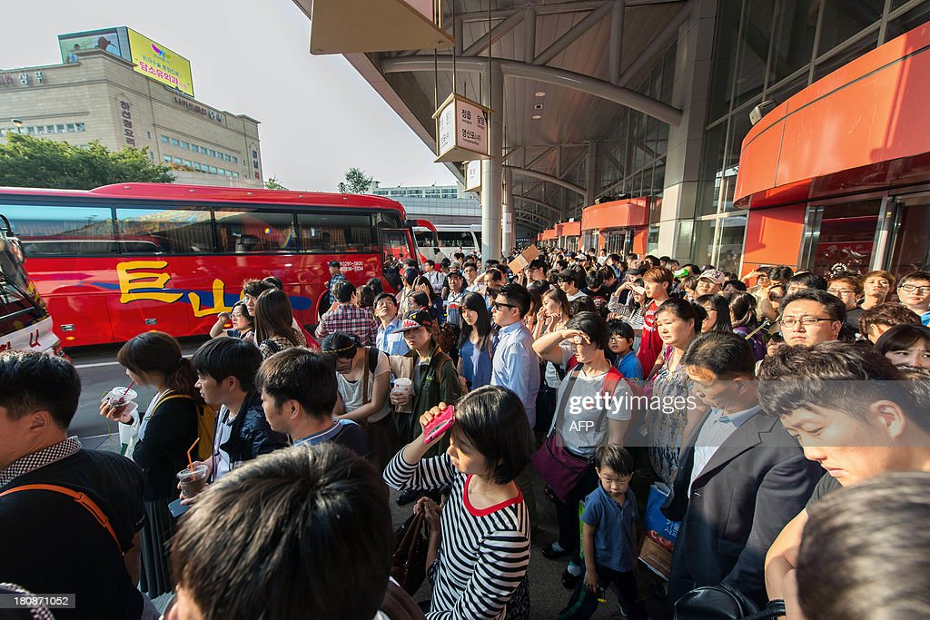 South Korean passengers queue for buses at a bus terminal in
