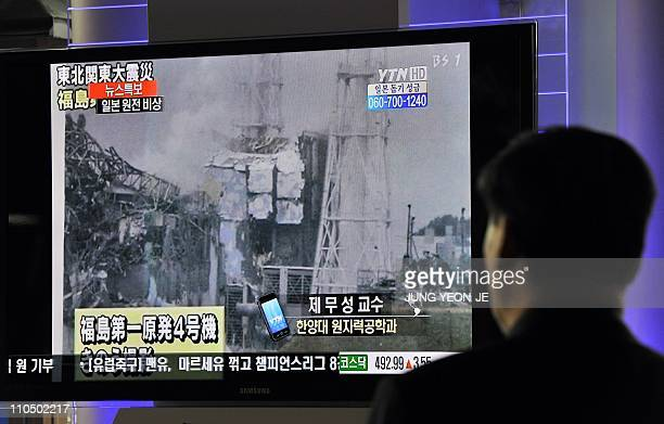 South Korean passengers walk past a TV reporting an explosion and feared meltdown of Japan's FukushimaDaiichi Nuclear Power Plant after a massive...