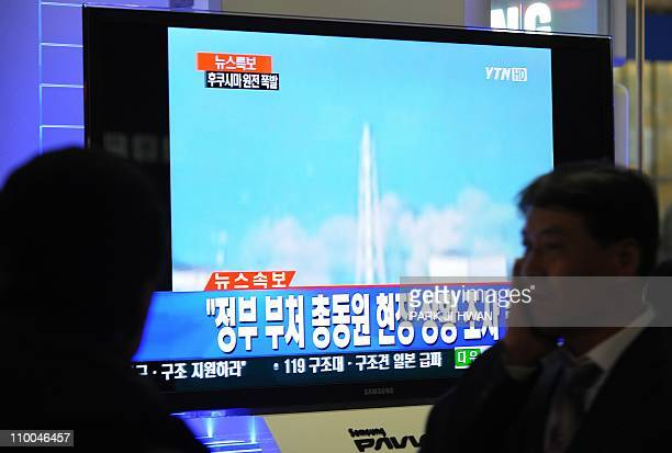 South Korean passengers watch TV showing Japan's Fukushima No 1 atomic plant spewing fumes amid reports that a meltdown is feared after a massive...
