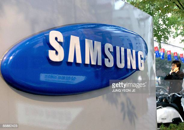 South Korean pedestrian walks by a logo of Samsung group in Seoul 09 October 2005 as domestic woes are mounting for Samsung South Korea's biggest and...
