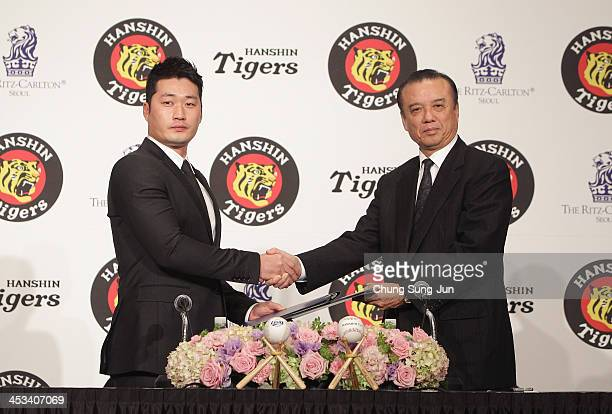 South Korean Pitcher Oh SeungHwan shakes hands with Hanshin Tigers general manager Nakamura Katsuhiro during the press conference at Ritz Carlton...