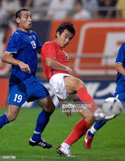 South Korean player Lee DongGook kicks the ball as Uzbekistan's Islom Inomov looks on during a friendly match against Uzbekistan part of the...