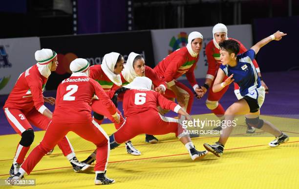 South Korean player tries to score as Iran players defend during the women's team Group B kabaddi match between Iran and South Korea at the 2018...