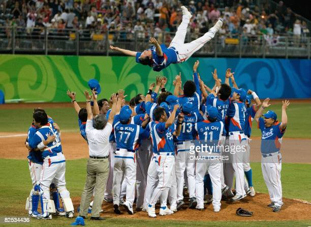 South Korean players toss manager Kim Kyungmoon into the air as they celebrate their victory over Cuba in their men's final game at the 2008 Beijing...