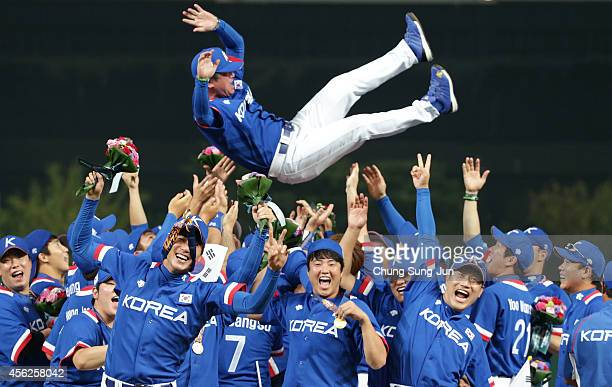 South Korean players tosse the manager Ryu JoongIl into the air during the victory ceremony over Chinese Taipei in the Baseball Final between South...