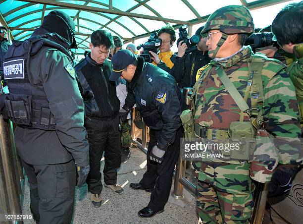 South Korean police and marines check a passenger before he departs from the port on Yeonpyeong Island on November 29 2010 A grimfaced South Korean...