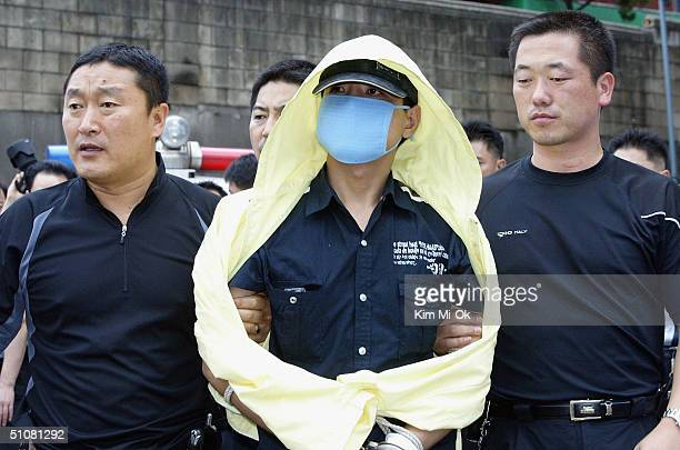 South Korean police escort suspected serial killer Yoo YoungChul during an inspection of suspected murder sites on July 19 2004 in Seoul South Korea...