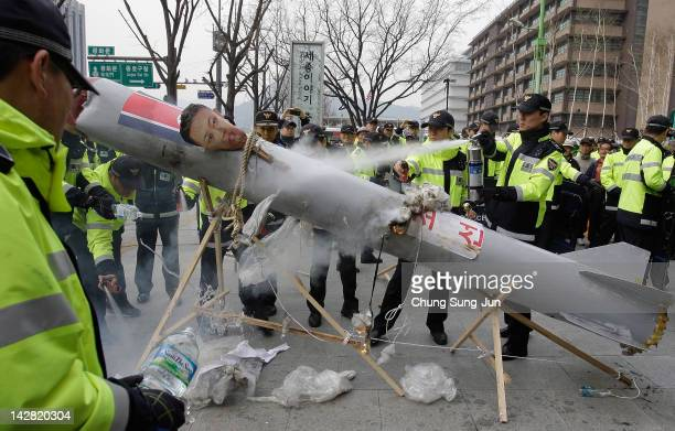 South Korean police extinguish flames after protesters burned a mock up of North Korea's missile during an antiNorth Korea rally protesting against...