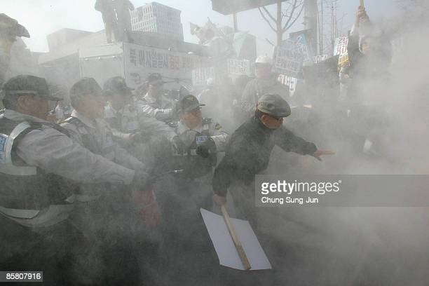 South Korean police extinguish flames after protesters burned a mock of North Korea's rocket during a rally against North Korea on April 5 in Seoul...