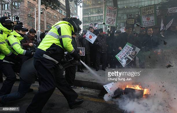 South Korean police extinguish flames after protesters burned placards during a antiJapan rally in front of the Japanese embassy on December 27 2013...