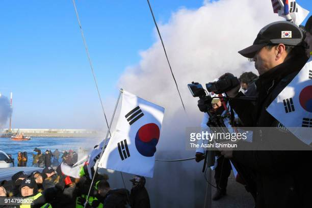 South Korean police officers spray tear gas toward protesters against the visit of North's art troupe prior to the arrival of the Mangyongbong 92...