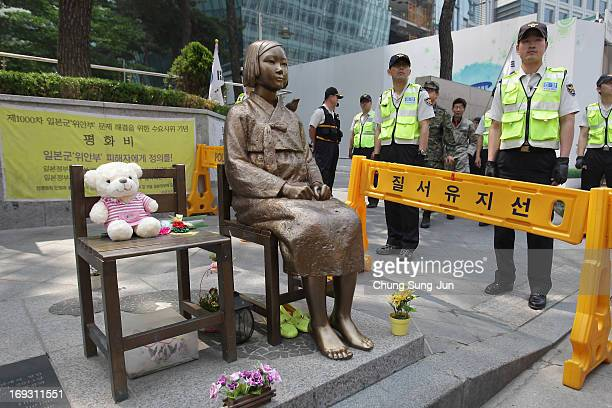 South Korean police stand guard beside a comfort women statue during a antiJapan rally in front of Japanese embassy on May 23 2013 in Seoul South...