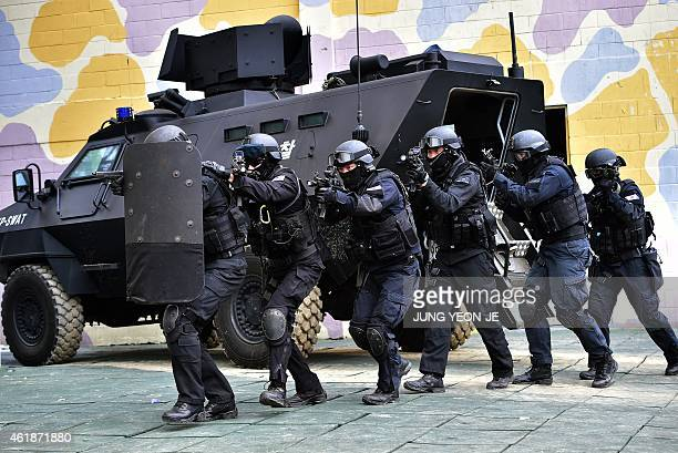 South Korean police SWAT team members move into a building during an antiterror drill in Seoul on January 21 2015 InterKorean tension remains high...