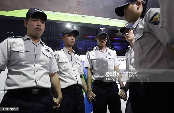 South Korean policemen stand guard as the North Korean national women football team arrive ahead of the 2013 EAFF East Asian Cup at the Incheon...