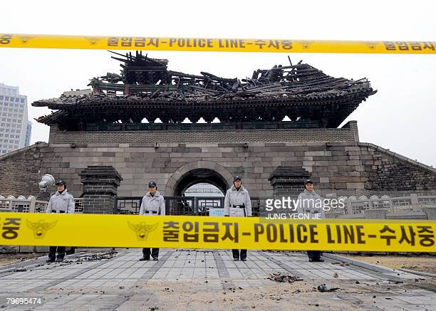 South korean policemen stand guard in front of the debris of the Namdaemun gate following a fire is seen in central Seoul on February 11 2008 One of...