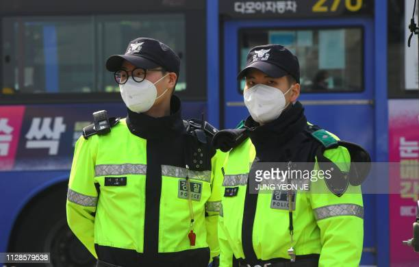 South Korean policemen wear face masks during heavily polluted weather in Seoul on March 4 2019 South Korean officials are advising the public to...
