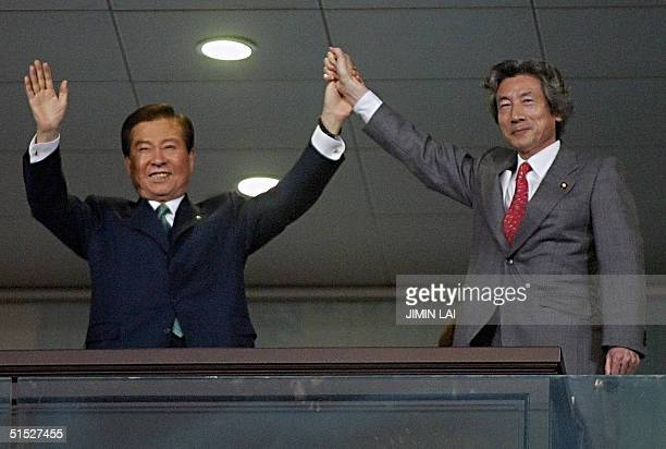 South Korean President Kim Dae-jung and Japanese Prime Minister Junichiro Koizumi hold hands during the official opening ceremony of the 2002 FIFA...