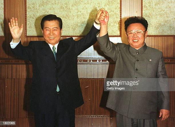 South Korean President Kim Dae-jung, left, and North Korean leader Kim Jong Il are all smiles June 14, 2000 as they raise their arms together at the...