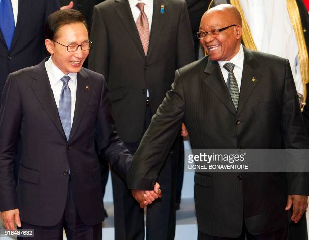 South Korean President Lee MyungBak and South African President Jacob Zuma hold hands before a family photo on November 3 2011 during the G20 Summit...
