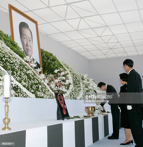 South Korean President Lee Myungbak burns incense as his wife Kim Yoonok observes during the funeral of the late former President Kim Daejung at the...